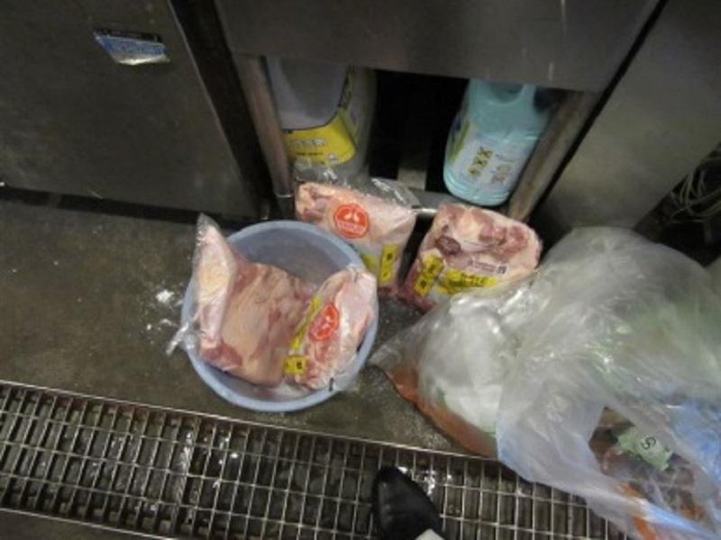 常温解凍中の生肉が床に直置きされています。床は汚染されており、また常温解凍や溜め水解凍では肉の表面温度と内部の温度差が出る為、雑菌が繁殖してしまいます。脇にはごみ袋、後ろには化学薬品があるため、食材が汚染される危険な要因が取り巻いています。解凍は冷蔵庫内でお願いします。