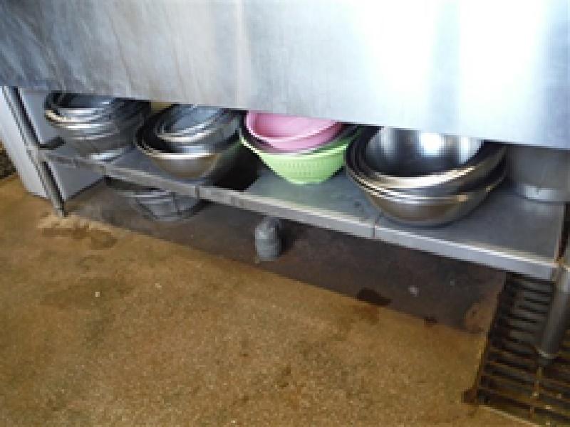 調理器具類の低位置や直置き保管が見られ、保管棚には汚れがあります。 床は汚染されている場所です。床からの水の跳ね返りやほこりにより調理器具類が汚染されます。高さを確保した衛生的な場所での保管、汚染防止シートの設置、直置きはしない、保管場所の定期的な清掃をするといったことが重要です。